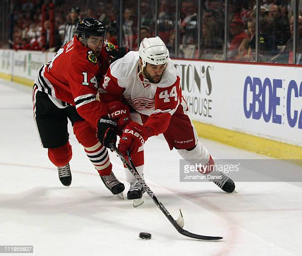 Chris Campoli of the Chicago Blackhawks and Todd Bertuzzi of the Detroit Red Wings battle for the puck at the United Center on April 10 2011 in...