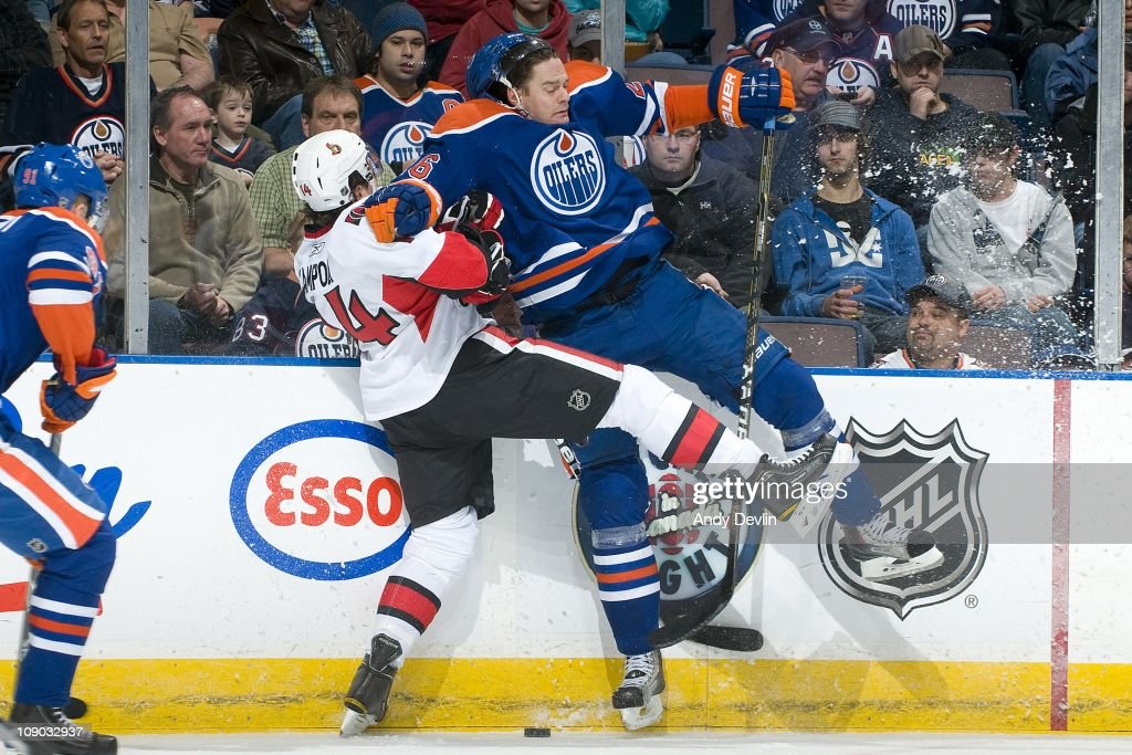 Chris Campoli of the Ottawa Senators takes a hard hit from Kurtis Foster of the Edmonton Oilers at Rexall Place on February 12 2011 in Edmonton...