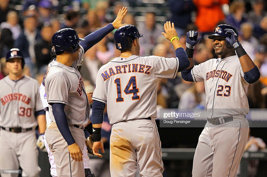 Chris Carter of the Houston Astros is welcomed home by Carlos Pena of the Houston Astros and JD Martinez of the Houston Astros who scored on Carter's...