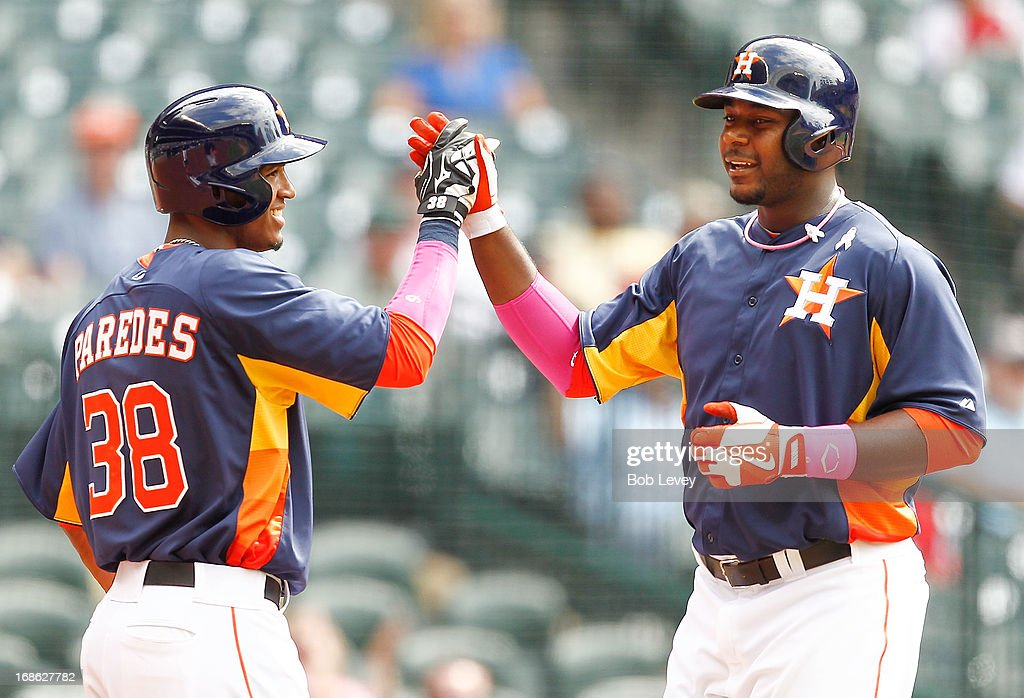 Chris Carter #23 of the Houston Astros receives a high five from Jimmy Paredes #38 of the Houston Astros after hitting a home run against the Texas Rangers at Minute Maid Park on May 12, 2013 in Houston, Texas.