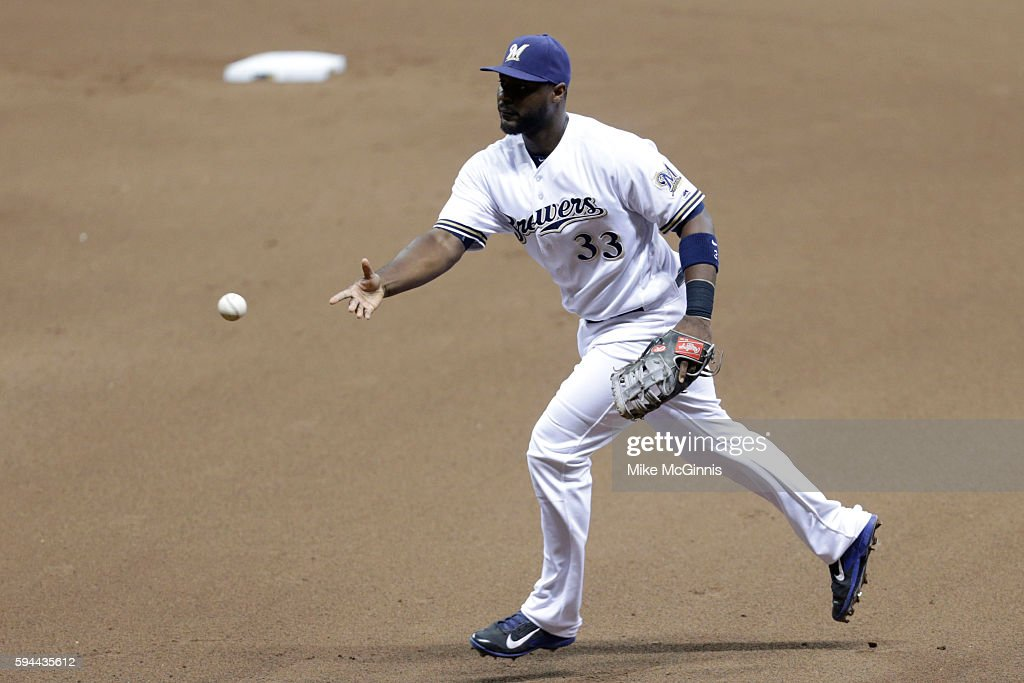 Chris Carter of the Milwaukee Brewers makes the flip to first base to retire Charlie Blackmon during the third inning against the Colorado Rockies at...