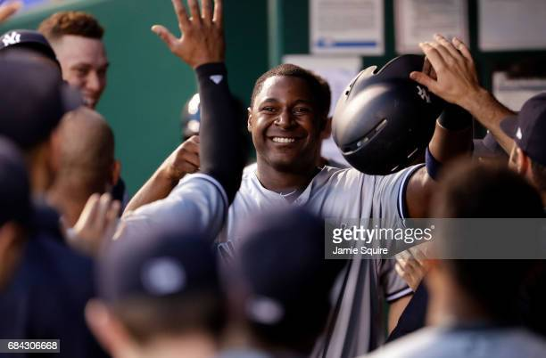 Chris Carter of the New York Yankees is congratulated by teammates in the dugout after scoring during the 4th inning of the game against the Kansas...