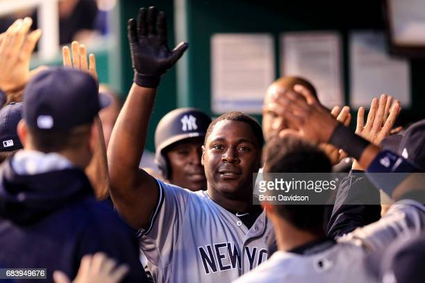 Chris Carter of the New York Yankees is congratulated by teammates after hitting a tworun home run against the Kansas City Royals during the fourth...