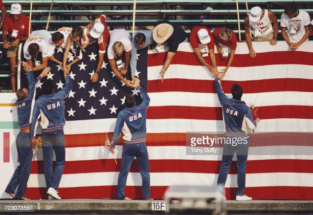 Chris Cavanaugh Robin Leamy David McCagg and Rowdy Gaines of the United States celebrate with fans in front of a large stars and stripes flag of the...