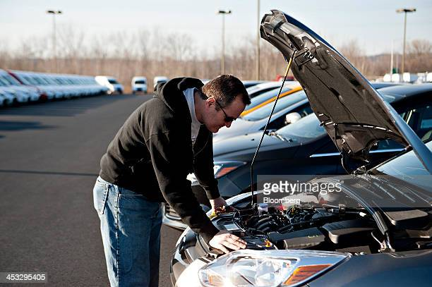 Chris Celiberti looks over the engine compartment of a 2014 Ford Motor Co Focus at Uftring Ford in East Peoria Illinois US on Saturday Nov 30 2013...