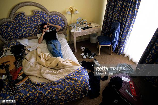 Chris Cheney of The Living End relaxes in a hotel room whilst on the road with AC/DC at the Swiss Grand Hotel on an unknown date in January 2001 in...