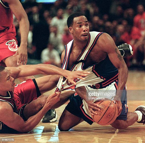 Chris Childs of the New York Knicks holds the ball as PJ Brown of the Miami Heat grabs onto his jersey in the third game of their first round NBA...