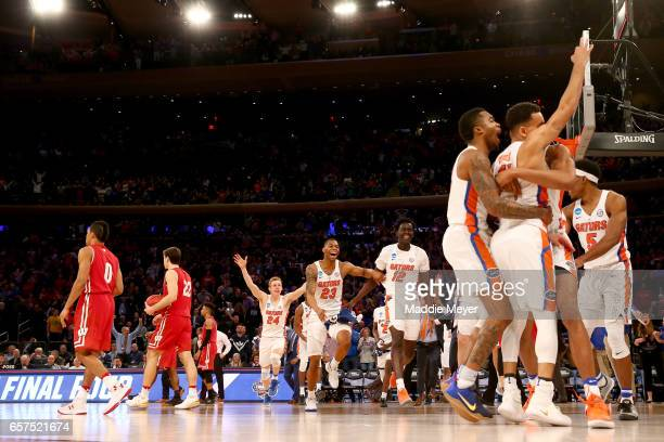 Chris Chiozza of the Florida Gators celebrates with his teammates after hitting the game winning three point basket in overtime to defeat the...