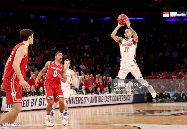 Chris Chiozza of the Florida Gators shoots a game winning three point basket in overtime to defeat the Wisconsin Badgers with a score of 84 to 83...