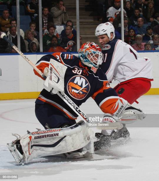 Chris Clark of the Columbus Blue Jackets is stopped by Dwayne Roloson of the New York Islanders at the Nassau Coliseum on December 29 2009 in...