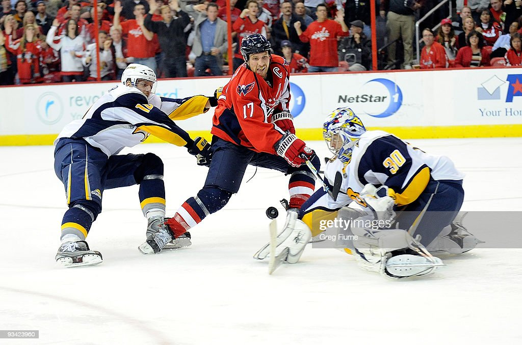Chris Clark of the Washington Capitals shoots the puck past Ryan Miller of the Buffalo Sabres at the Verizon Center on November 25 2009 in Washington...