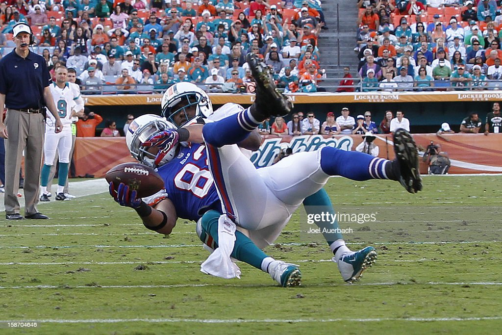Chris Clemons #30 of the Miami Dolphins tackles Ruvell Martin #82 of the Buffalo Bills on December 23, 2012 at Sun Life Stadium in Miami Gardens, Florida. The Dolphins defeated the Bills 24-10.