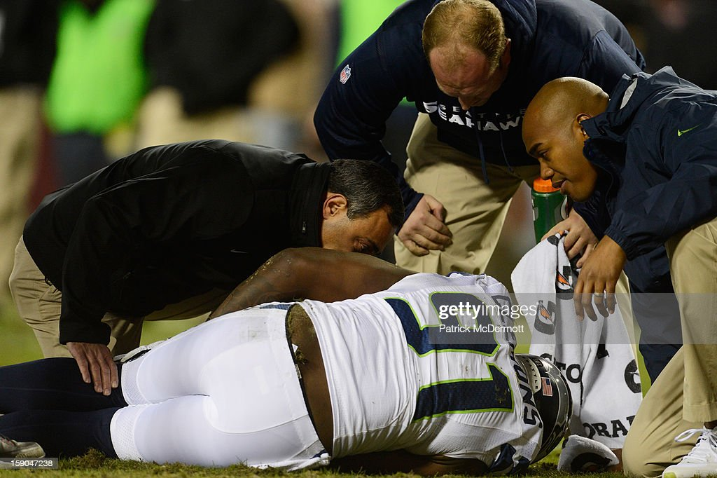 Chris Clemons #91 of the Seattle Seahawks receives attention after being injured on a play against the Washington Redskins during the NFC Wild Card Playoff Game at FedExField on January 6, 2013 in Landover, Maryland.