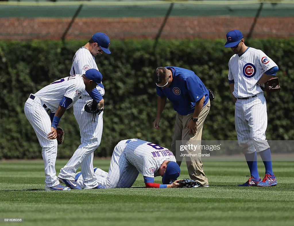 Chris Coghlan of the Chicago Cubs is attened to after hurting his shoulder against the Milwaukee Brewers at Wrigley Field on August 16 2016 in...