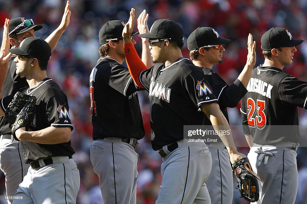 Chris Coghlan #8 (L) of the Miami Marlins celebrates with teammates including Giancarlo Stanton #27 (C) and Jake Marisnick #23 (R) after beating hte Washington Nationals 4-2 in game 1 of their day-night doubleheader at Nationals Park on September 22, 2013 in Washington, DC.