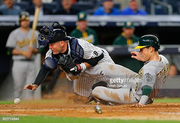 Chris Coghlan of the Oakland Athletics scores on a double by Josh Reddick as catcher Brian McCann of the New York Yankees reaches back for the ball...