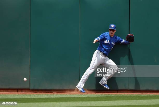 Chris Coghlan of the Toronto Blue Jays can not catch a ball hit by Rajai Davis of the Oakland Athletics in the fifth inning at Oakland Alameda...