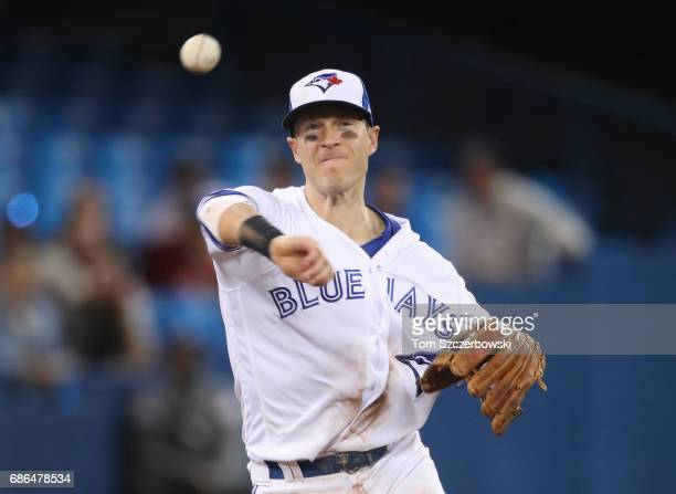 Chris Coghlan of the Toronto Blue Jays throws out the baserunner in the ninth inning during MLB game action against the Atlanta Braves at Rogers...