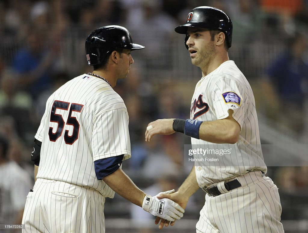 Chris Colabello #55 congratulates teammate Joe Mauer #7 of the Minnesota Twins on scoring a run against the Houston Astros during the seventh inning of the game on August 3, 2013 at Target Field in Minneapolis, Minnesota. The Twins defeated the Astros 6-4.