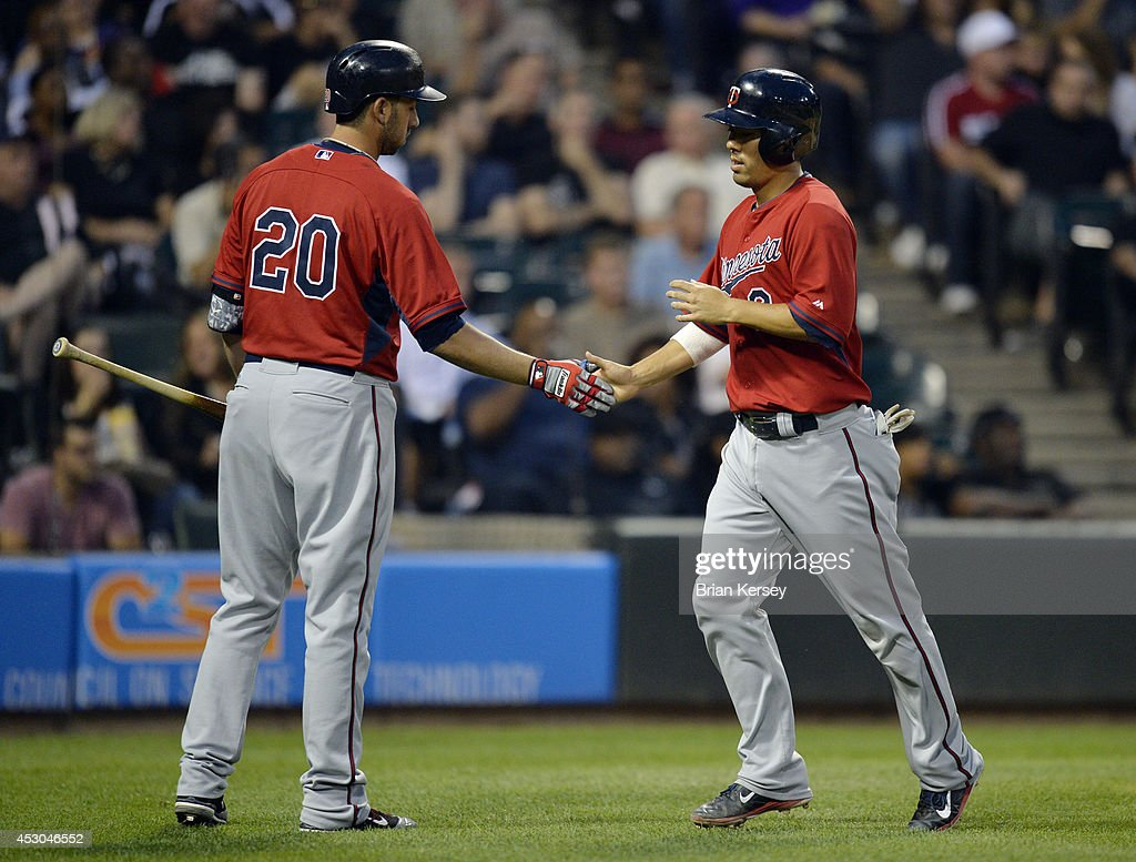 Chris Colabello #20 of the Minnesota Twins (L) congratulates teammate Brian Dozier #2 after Dozier scored on an RBI single hit by Josh Willingham during the third inning against the Chicago White Sox at U.S. Cellular Field on August 1, 2014 in Chicago, Illinois.