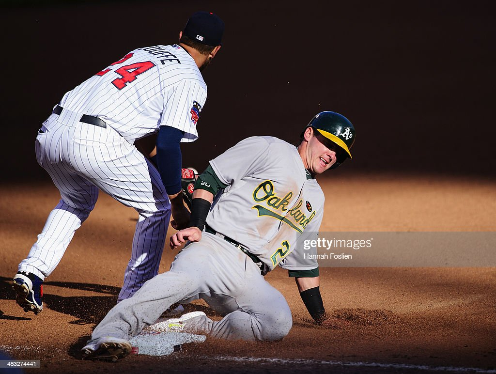 Chris Colabello #20 of the Minnesota Twins slides in safely to third base as <a gi-track='captionPersonalityLinkClicked' href=/galleries/search?phrase=Trevor+Plouffe&family=editorial&specificpeople=5722348 ng-click='$event.stopPropagation()'>Trevor Plouffe</a> #24 of the Minnesota Twins fields the ball during the seventh inning of the home opening game on April 7, 2014 at Target Field in Minneapolis, Minnesota. The Athletics defeated the Twins 8-3.