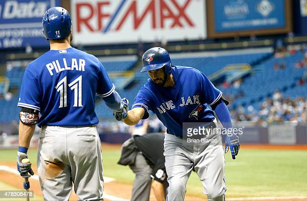 Chris Colabello of the Toronto Blue Jays celebrates with teammate Kevin Pillar following his home run on line drive to center field off of pitcher...