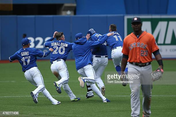 Chris Colabello of the Toronto Blue Jays is congratulated by teammates after hitting a gamewinning tworun single in the ninth inning during MLB game...