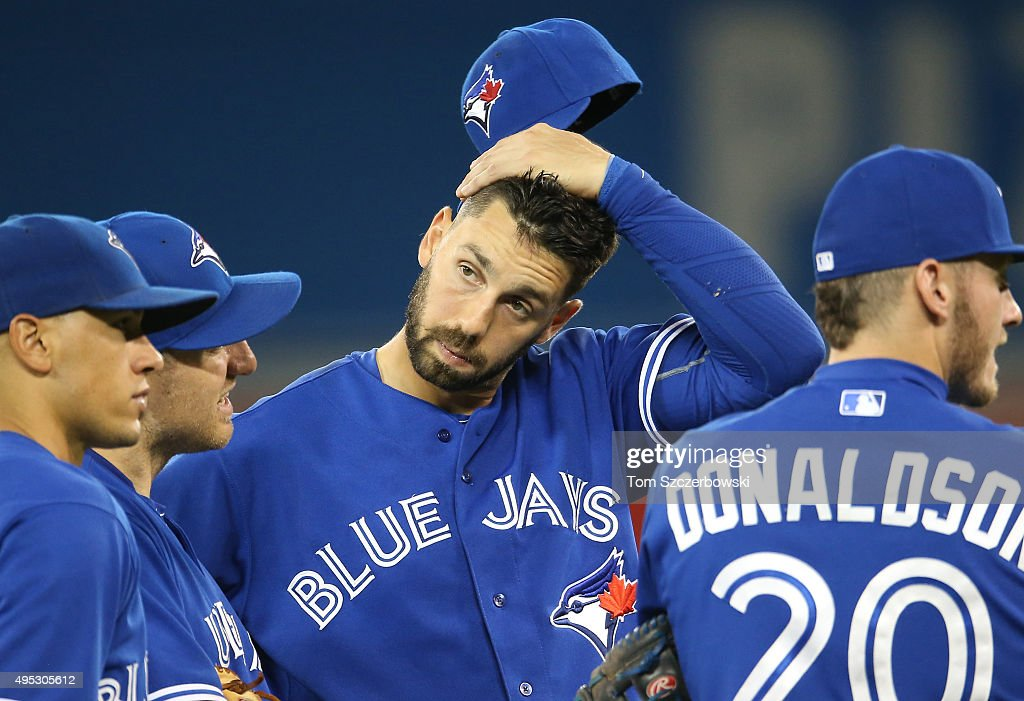 Chris Colabello of the Toronto Blue Jays looks on during a pitching change with Ryan Goins and Cliff Pennington and Josh Donaldson during MLB game...