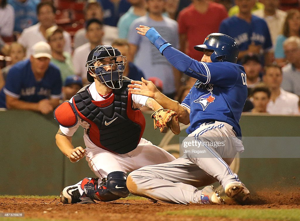 Chris Colabello #15 of the Toronto Blue Jays scores as Blake Swihart #23 of the Boston Red Sox is unable to make the play at the plate in the tenth inning at Fenway Park on September 8, 2015 in Boston, Massachusetts.