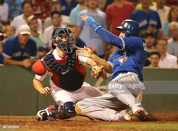 Chris Colabello of the Toronto Blue Jays scores as Blake Swihart of the Boston Red Sox is unable to make the play at the plate in the tenth inning at...