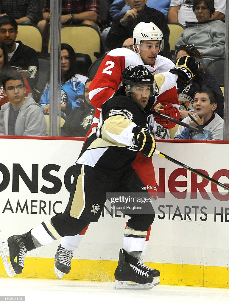 Chris Connor # 23 of Pittsburgh Penguins checks Brendan Smith # 2 of the Detroit Red Wings during the first period of a preseason game on September 16, 2013 at the CONSOL Energy Center in Pittsburgh, Pennsylvania.
