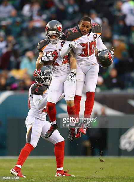 Chris Conte of the Tampa Bay Buccaneers celebrates his interception thrown my quarterback Mark Sanchez of the Philadelphia Eagles with teammate...