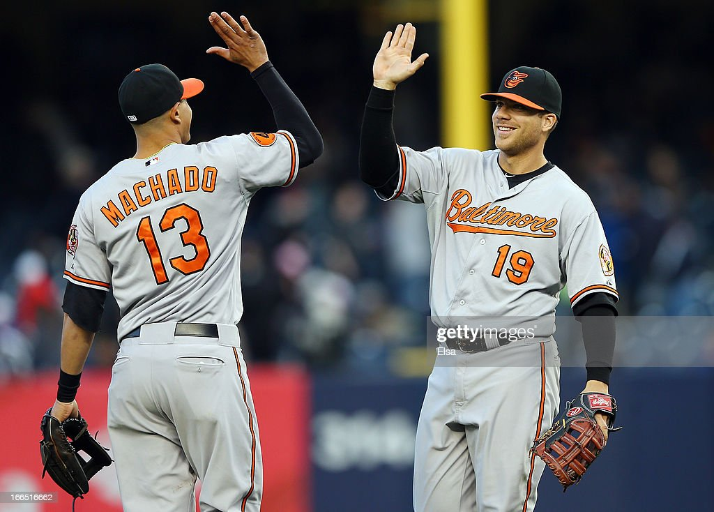 Chris Davis #19 and <a gi-track='captionPersonalityLinkClicked' href=/galleries/search?phrase=Manny+Machado&family=editorial&specificpeople=5591039 ng-click='$event.stopPropagation()'>Manny Machado</a> #13 of the Baltimore Orioles celebrate the win over the New York Yankees on April 13, 2013 at Yankee Stadium in the Bronx borough of New York City.The Baltimore Orioles defeated the New York Yankees 5-3.