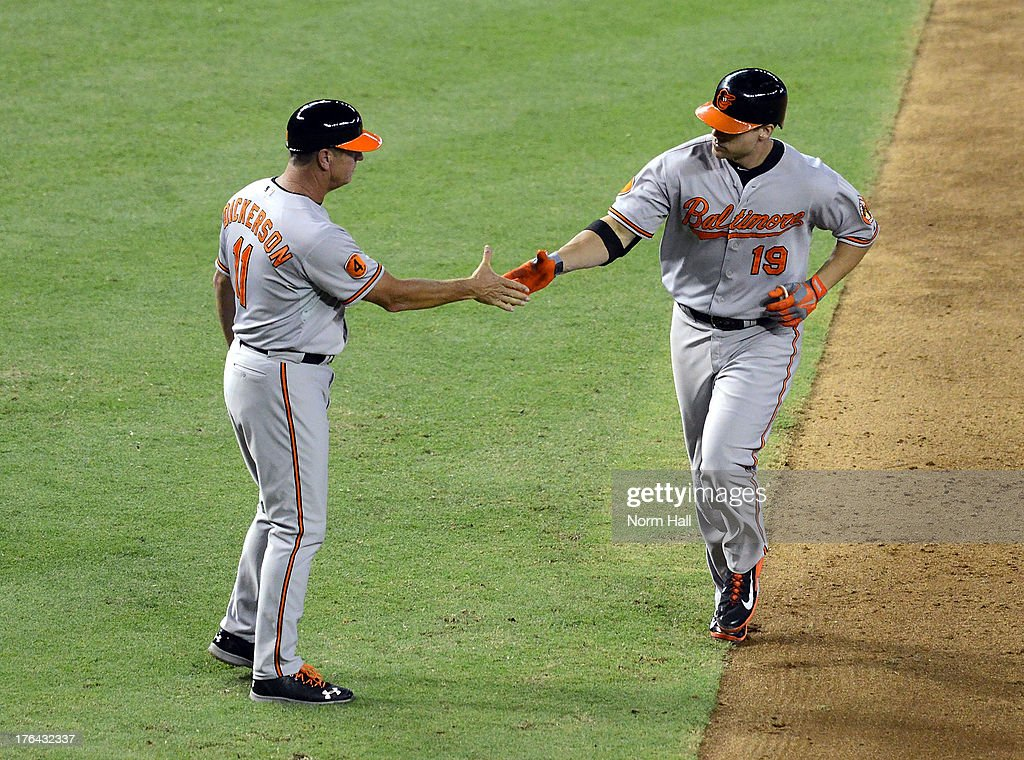 Chris Davis #19 and third base coach Bobby Dickerson #11 of the Baltimore Orioles celebrate Davis' home run against the Arizona Diamondbacks at Chase Field on August 12, 2013 in Phoenix, Arizona.