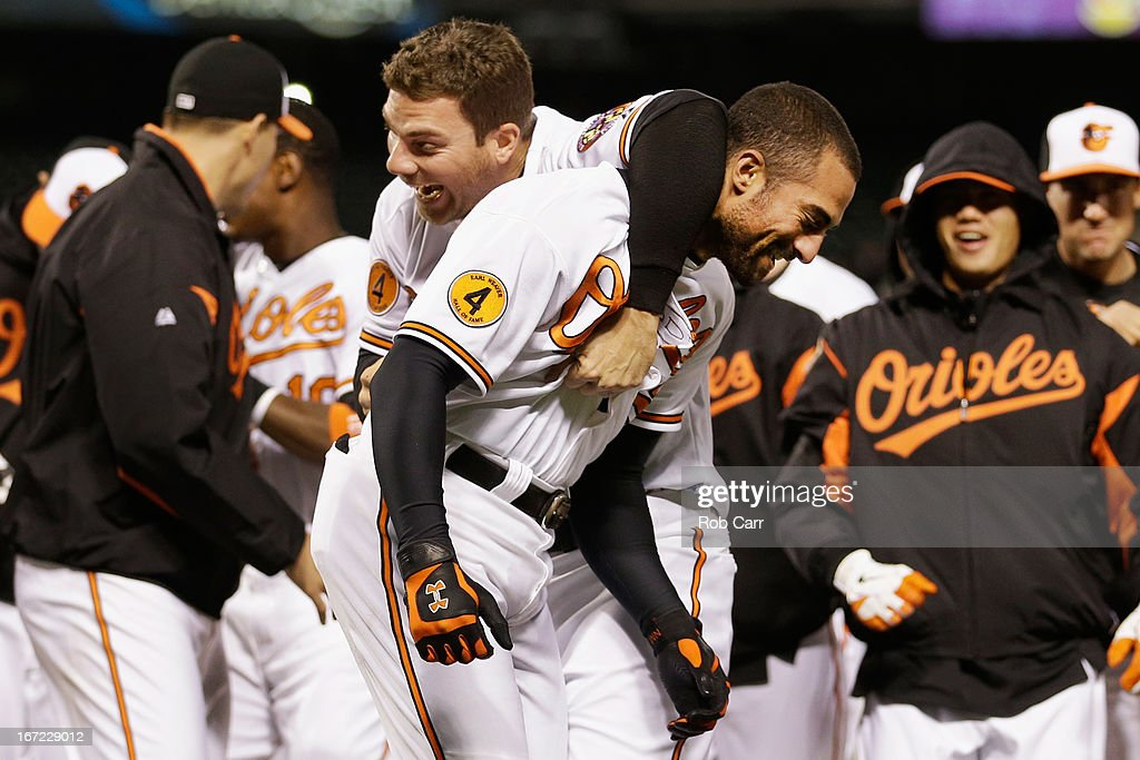 Chris Davis celebrates with Nick Markakis of the Baltimore Orioles after Markakis drove in Davis for the game winning run to defeat the Toronto Blue...