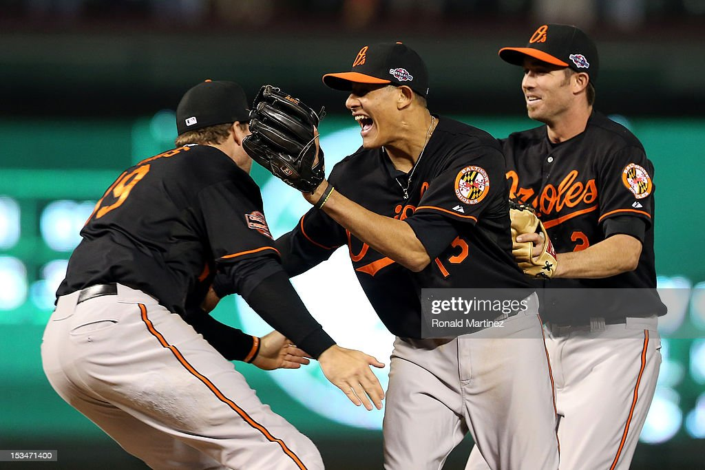 Chris Davis #19, Manny Machado #13 and J.J. Hardy #2 of the Baltimore Orioles celebrate after they won 5-1 against the Texas Rangers during the American League Wild Card playoff game at Rangers Ballpark in Arlington on October 5, 2012 in Arlington, Texas.