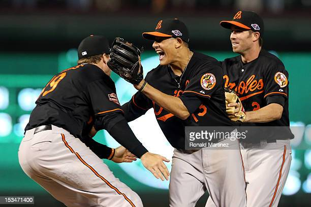 Chris Davis Manny Machado and JJ Hardy of the Baltimore Orioles celebrate after they won 51 against the Texas Rangers during the American League Wild...