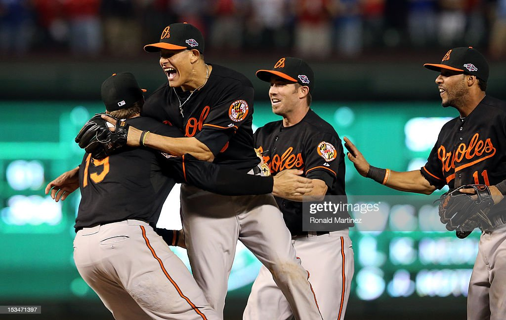 Chris Davis #19, Manny Machado #13, J.J. Hardy #2 and Robert Andino #11 of the Baltimore Orioles celebrate after they won 5-1 against the Texas Rangers during the American League Wild Card playoff game at Rangers Ballpark in Arlington on October 5, 2012 in Arlington, Texas.