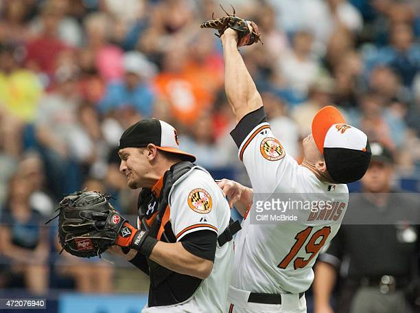 Chris Davis of the Baltimore Orioles and Caleb Joseph of the Baltimore Orioles bump one another as Davis makes the catch against the Tampa Bay Rays...