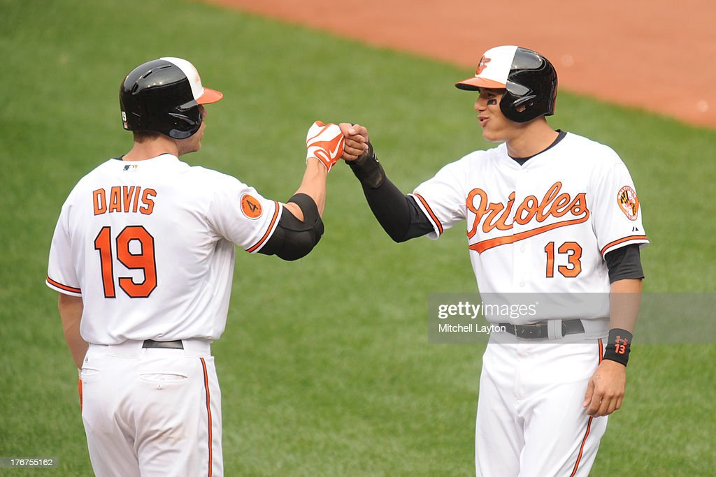 Chris Davis #19 of the Baltimore Orioles celebrates a two-run home run with <a gi-track='captionPersonalityLinkClicked' href=/galleries/search?phrase=Manny+Machado&family=editorial&specificpeople=5591039 ng-click='$event.stopPropagation()'>Manny Machado</a> #13 of the Baltimore Orioles in the eighth inning during a baseball game against the Colorado Rockies on August 18, 2013 at Oriole Park at Camden Yards in Baltimore, Maryland. The Orioles won 7-2.