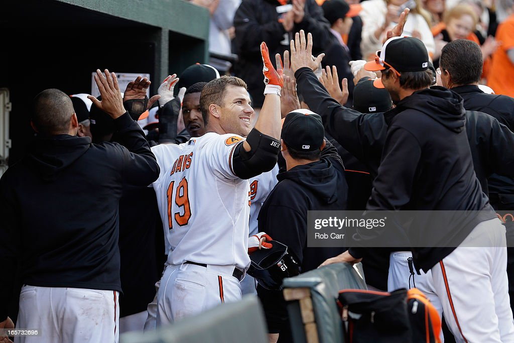 Chris Davis #19 of the Baltimore Orioles celebrates in the dugout after hitting an eighth inning grand slam home run against the Minnesota Twins during the Orioles 9-6 opening day win at Oriole Park at Camden Yards on April 5, 2013 in Baltimore, Maryland.