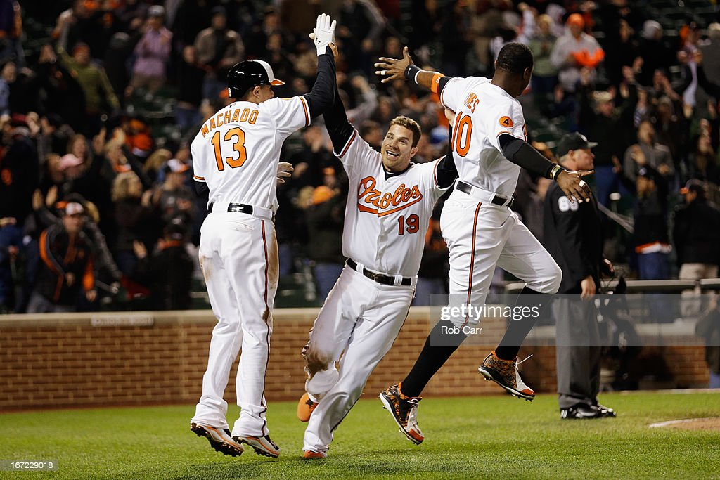 Chris Davis #19 of the Baltimore Orioles celebrates scoring the game winning run with <a gi-track='captionPersonalityLinkClicked' href=/galleries/search?phrase=Manny+Machado&family=editorial&specificpeople=5591039 ng-click='$event.stopPropagation()'>Manny Machado</a> #13 and Adam Jones #10 during the Orioles 2-1 win over the Toronto Blue Jays at Oriole Park at Camden Yards on April 22, 2013 in Baltimore, Maryland.
