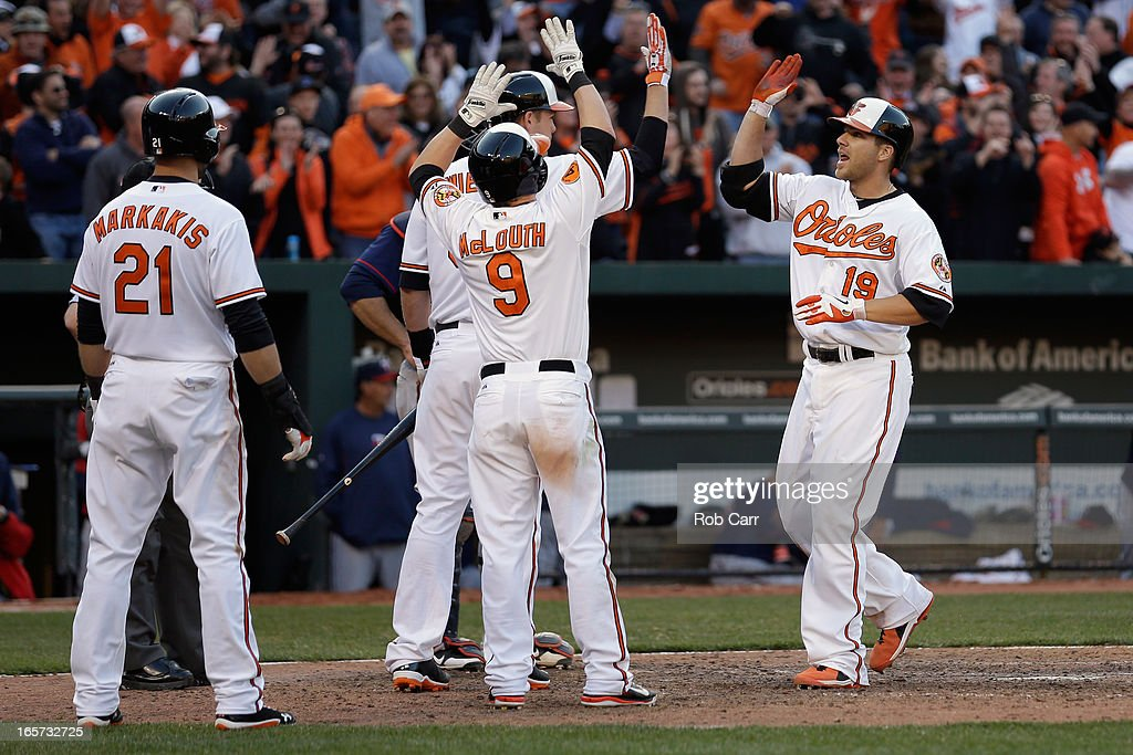 Chris Davis #19 of the Baltimore Orioles celebrates with Matt Wieters #32, Nate McLouth #9, and Nick Markakis #21 after hitting a grand slam home run against the Minnesota Twins during the eighth inning of the Orioles 9-5 opening day win at Oriole Park at Camden Yards on April 5, 2013 in Baltimore, Maryland.