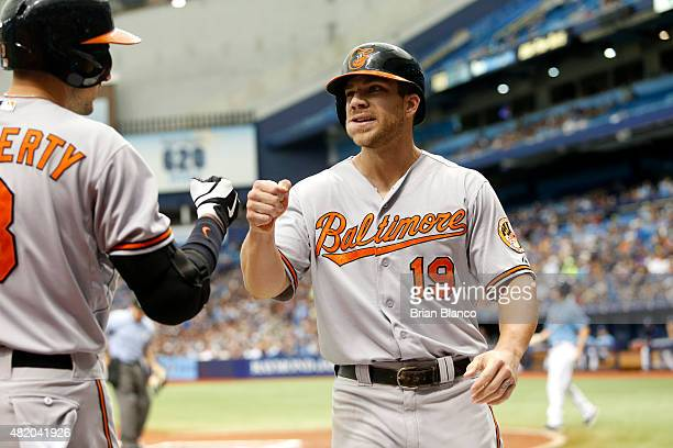 Chris Davis of the Baltimore Orioles celebrates with teammate Ryan Flaherty after scoring off of a single by JJ Hardy during the first inning of a...