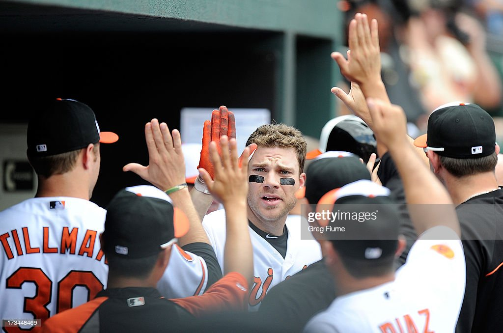 Chris Davis #19 of the Baltimore Orioles celebrates with teammates after hitting a home run in the third inning against the Toronto Blue Jays at Oriole Park at Camden Yards on July 14, 2013 in Baltimore, Maryland.