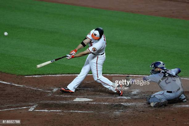 Chris Davis of the Baltimore Orioles follows hits a fourth inning grand slam as catcher Jonathan Lucroy of the Texas Rangers looks on at Oriole Park...