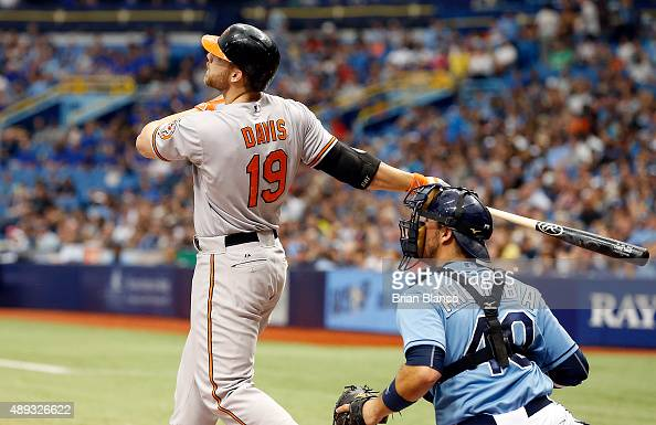 Chris Davis of the Baltimore Orioles follows through with his swing after hitting a tworun home run in front of catcher JP Arencibia of the Tampa Bay...