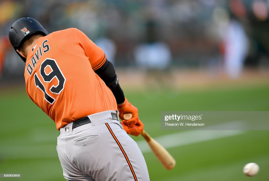 Chris Davis #19 of the Baltimore Orioles hits an rbi single scoring Trey Mancini #16 against the Oakland Athletics in the top of the first inning at Oakland Alameda Coliseum on August 12, 2017 in Oakland, California.