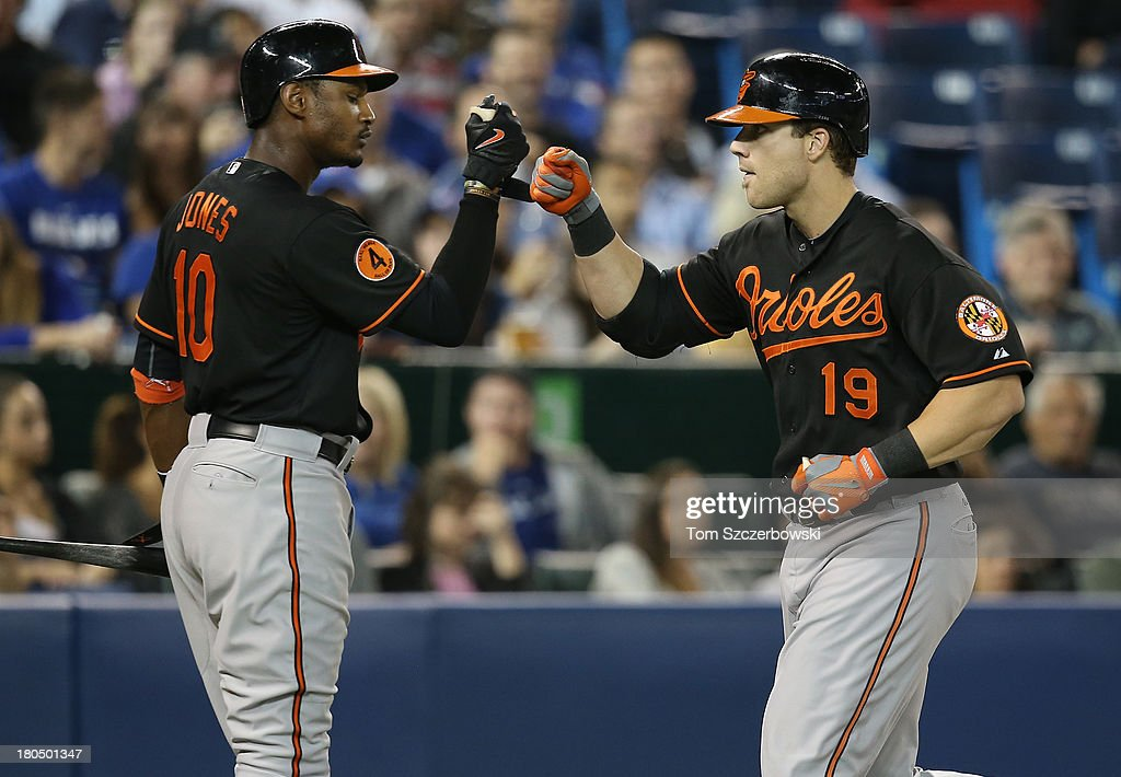 Chris Davis #19 of the Baltimore Orioles is congratulated by Adam Jones #10 after hitting his fiftieth home run of the season in the eighth inning connecting on a solo home run during MLB game action against the Toronto Blue Jays on September 13, 2013 at Rogers Centre in Toronto, Ontario, Canada.