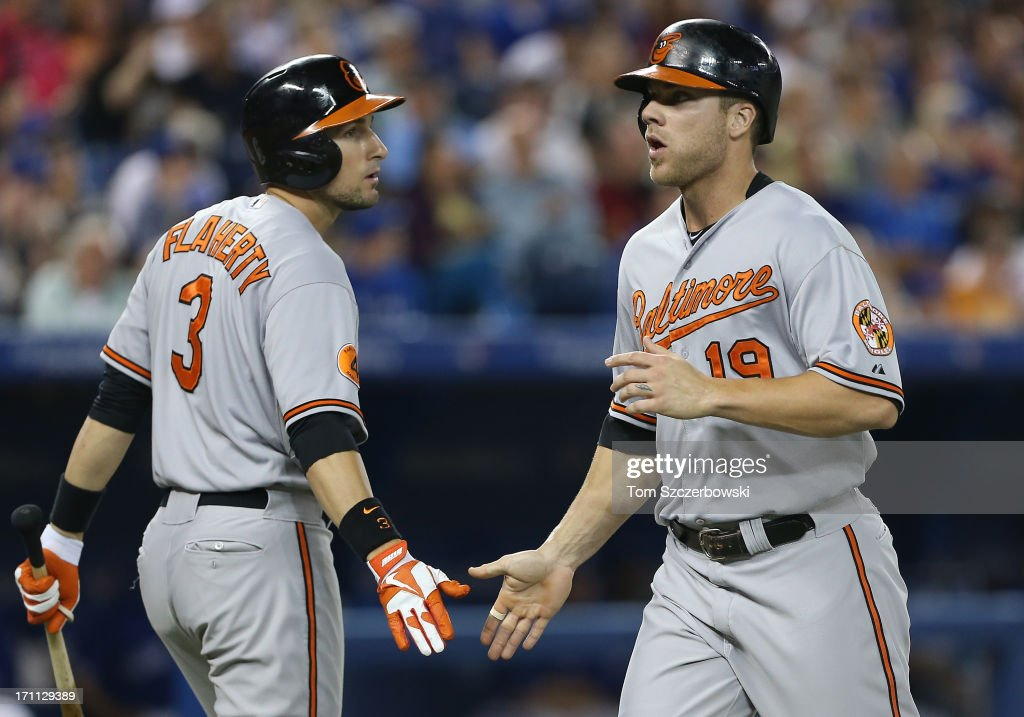 Chris Davis #19 of the Baltimore Orioles is congratulated by Ryan Flaherty #3 after scoring a run in the fifth inning during MLB game action against the Toronto Blue Jays on June 22, 2013 at Rogers Centre in Toronto, Ontario, Canada.